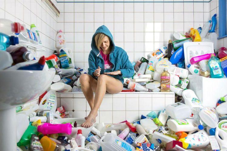 Une femme se vernie les ongles dans une salle de bain encombrée de bidons de lessives