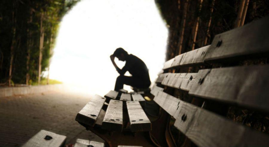 une homme assis sur un banc dans un tunnel se tient la tête