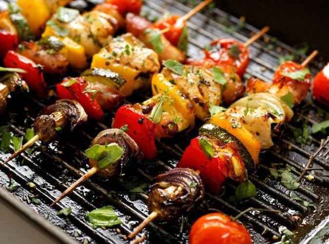 4 brochettes de légumes en train de cuire sur une grille de barbecue