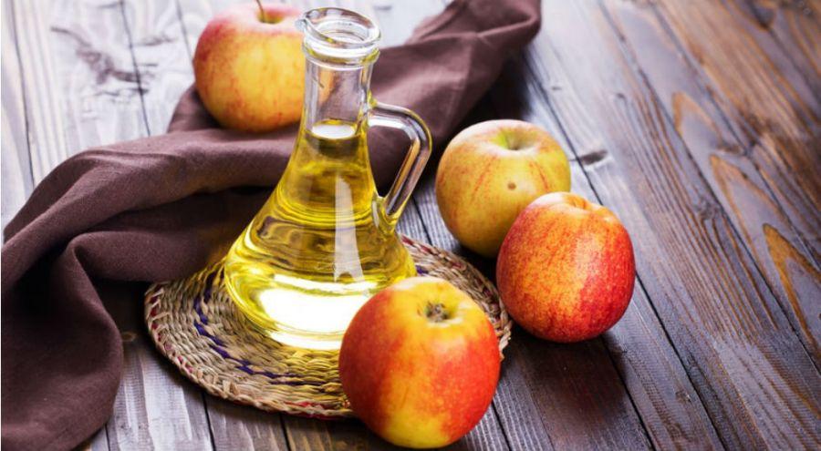 du vinaigre de cidre et des pommes sur une table