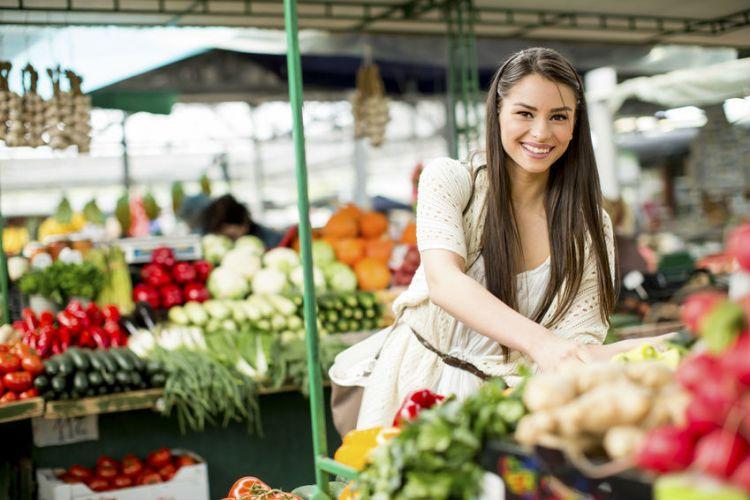 une femme choisit ses légumes au marché