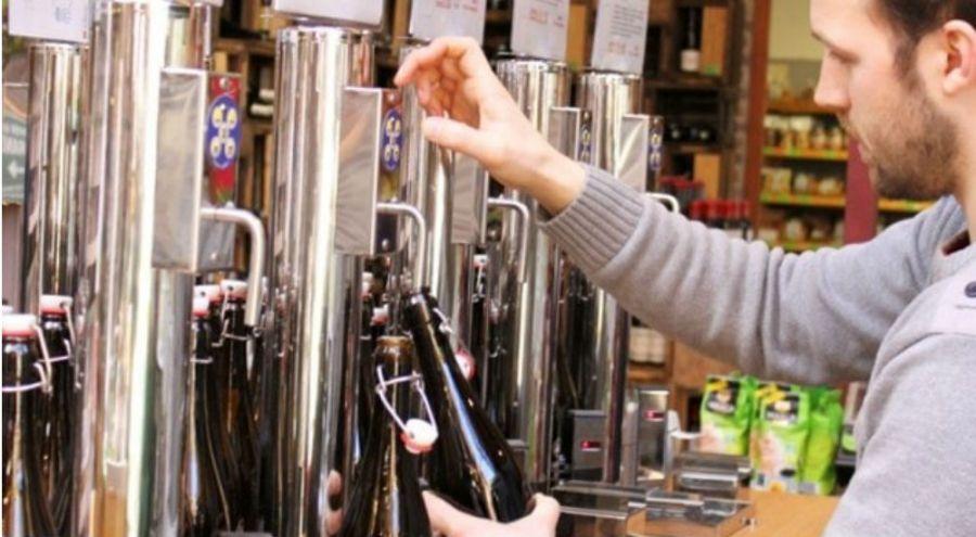 un homme remplit une bouteille en verre