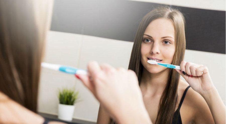 une femme se brosse les dents