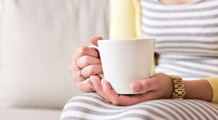 une femme tient une boisson chaude dans une tasse blanche