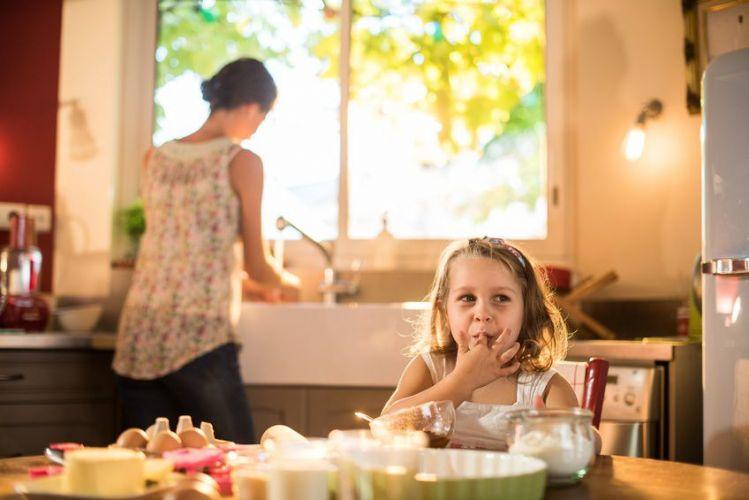 une petite fille mange de la pâte à gâteau pendant que sa mère a le dos tourné