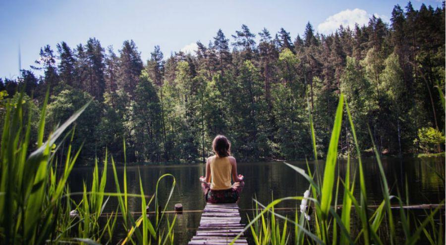 une femme médite sur un pont devant un lac et une forêt