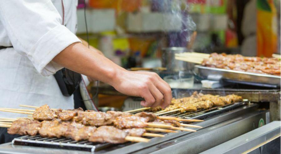 un chinois cuisine des brochettes