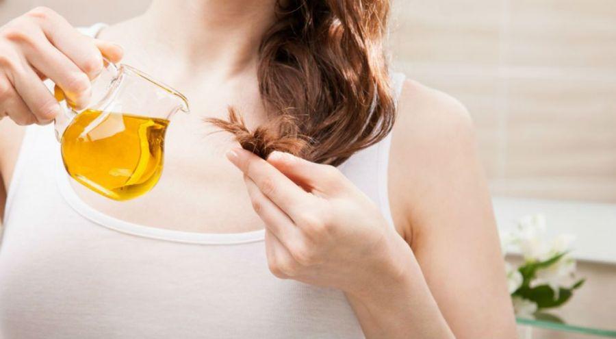une femme mettant de l'huile de moringa sur la pointe de ses cheveux