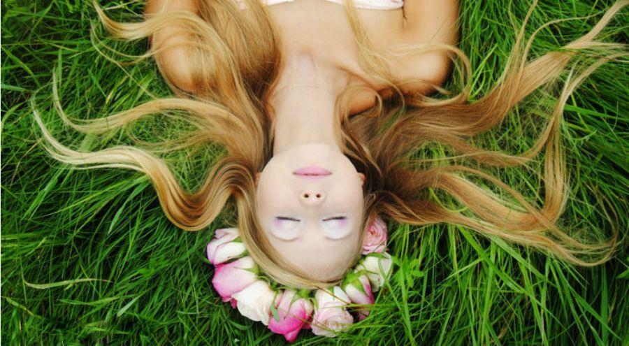 une femme aux longs cheveux allongée dans l'herbe