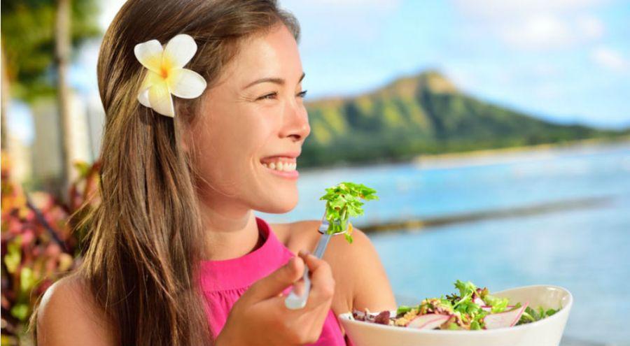 une femme mange au bord de la plage