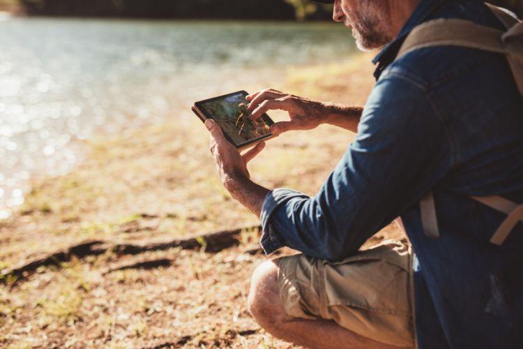 Un homme dans la nature tenant un smartphone