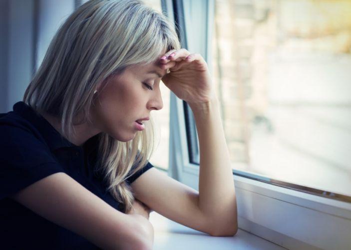 une femme stressant à la fenêtre