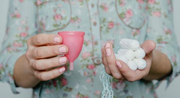 une femme tient une coupe menstruelle et des tampons
