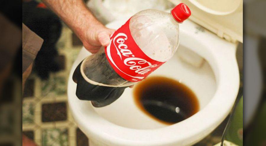 Un homme verse du Coca-Cola dans la cuvette des toilettes