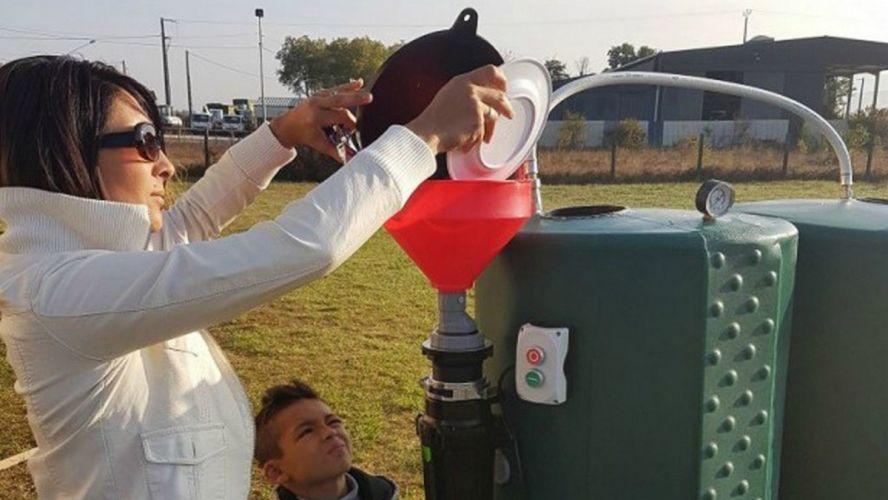 une femme en train de jeter des déchets organiques dans le méthaniseur domestique