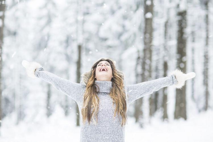 une femme les bras levés dans une forêt enneigée