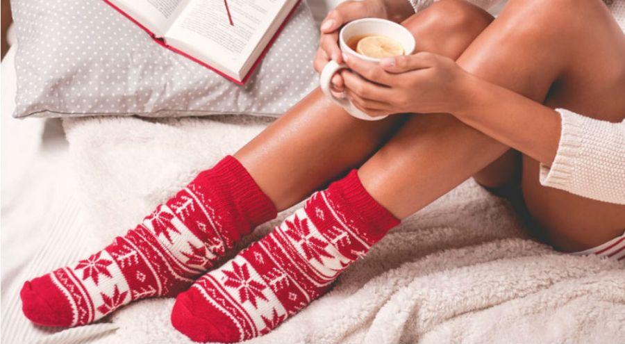 une femme boit une tisane chaude, lit un livre et porte des chaussettes de Noël