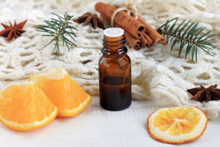 un flacon d'huile essentielle avec de l'orange et de la cannelle