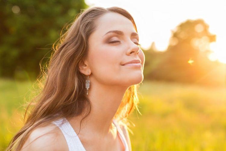 Une femme souriante en train de profiter du soleil