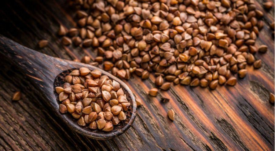 une cuillère en bois contenant des graines de sarrasin