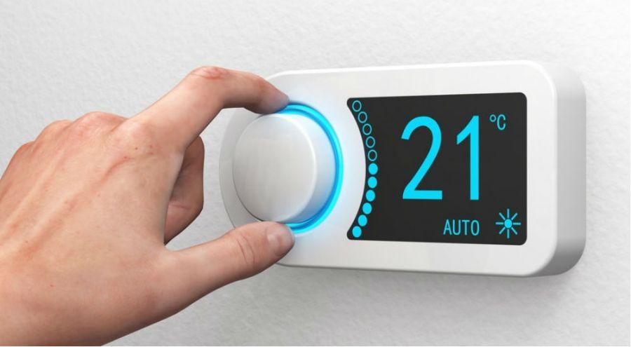 une personne règle son thermostat pour le chauffagr