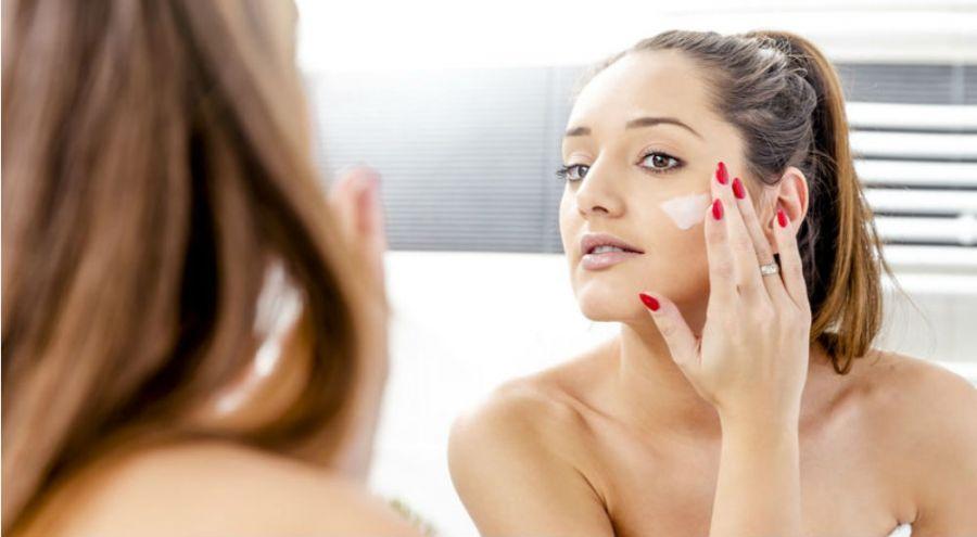 une femme se met de la crème hydratante sur le visage