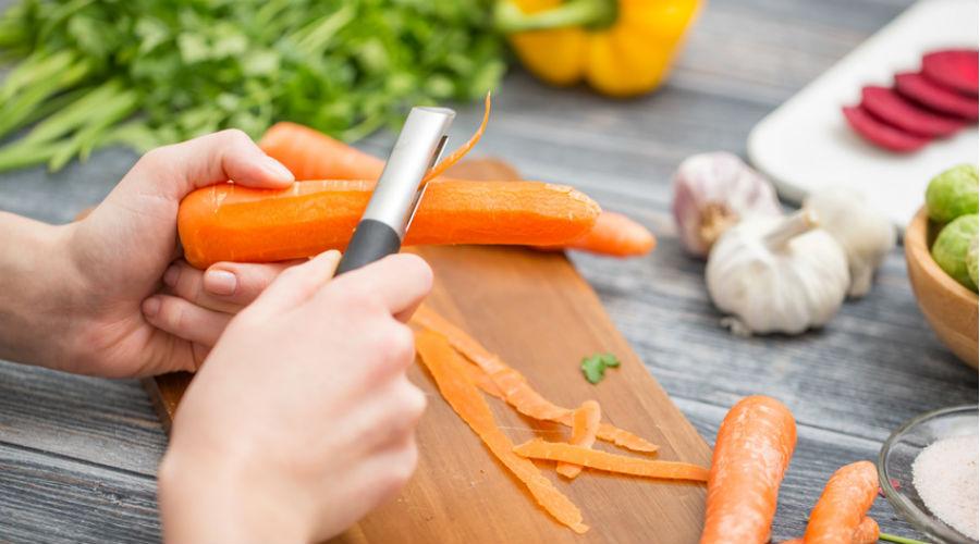 une personne épluche des carottes pour faire la cuisine
