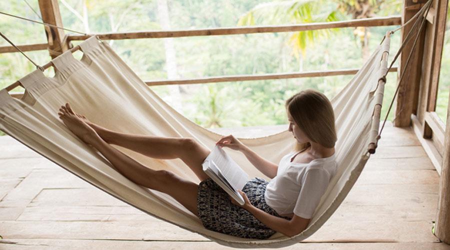 une femme en train de lire un livre dans son hammac