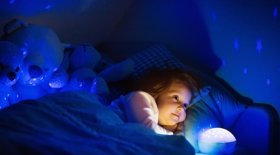 Une petite fille dans son lit avec une veilleuse