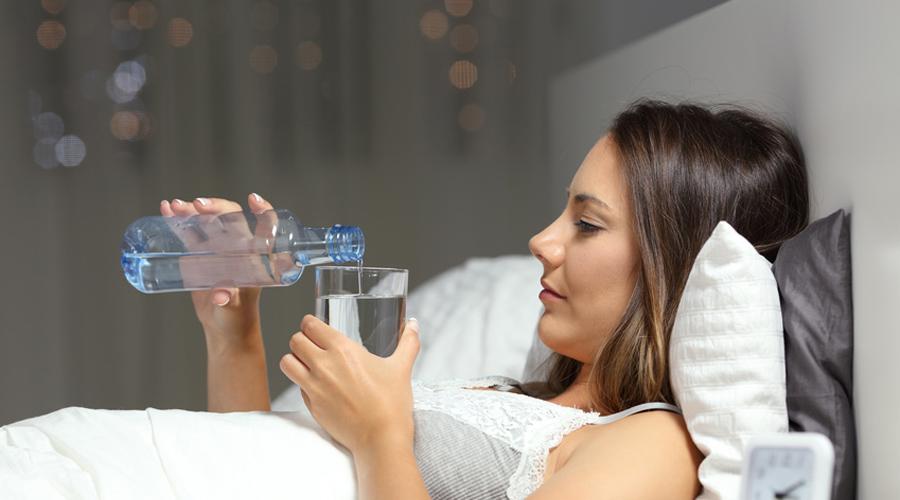 femme buvant de l'eau dans son lit