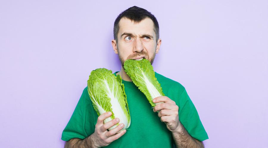 Un homme mange une feuille de salade d'un air interrogatif